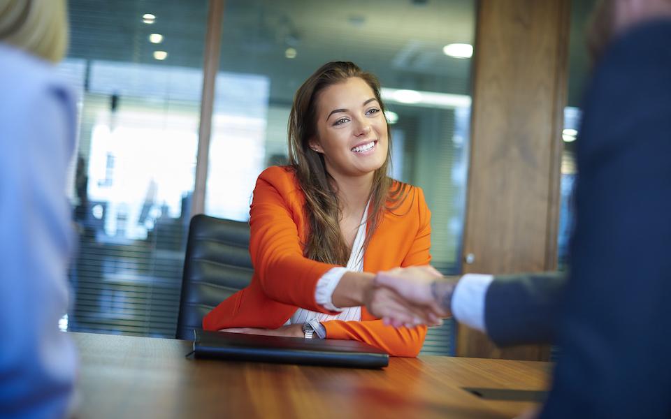 Jeune diplômée en entrevue serrant la main énergiquement avec son nouvel employeur